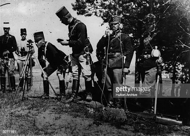 Austrian troops reconnoitring territory in the field, using a tripod-mounted telescope and field telephone.