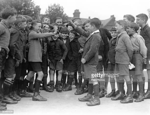 Boys in their uniform shorts and long socks conker fighting in the conker season in Hornsey London 1926