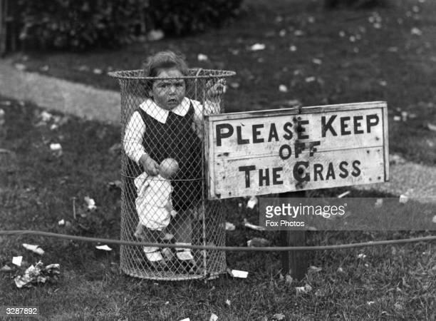 A child standing in a park rubbish bin
