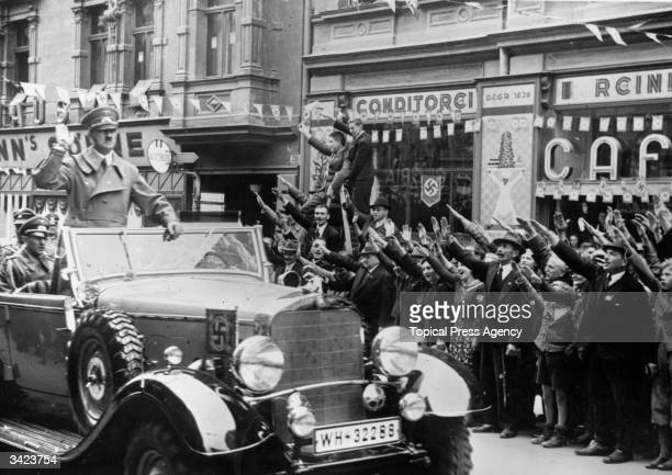 Adolf Hitler is greeted with the Nazi salute as he heads a convoy through Sudetenland which had become part of the Third Reich after the Munich Pact