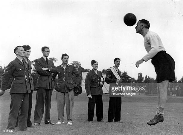 A group of RAF men watch as Carter leaps to head the ball during touch line practice The man throwing the ball is tennis coach Dan Maskell Original...