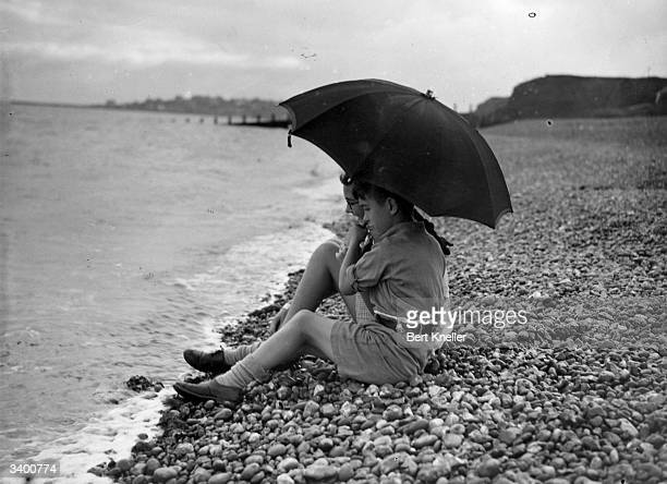 A young couple resting on a pebble beach