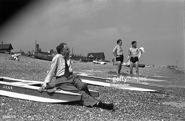 English novelist EM Forster takes a seat on the beach whilst composer Benjamin Britten and renowned tenor Peter Pears dry off after a dip in the sea...