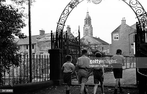 A group of boys passing under the elaborate metalwork gateway of a bridge in the Scottish industrial town of Kilmarnock Kilmarnock is home to a...