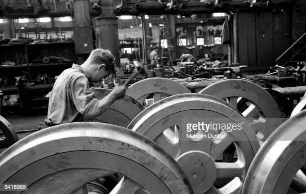 A worker attends to a large wheel in a factory in the Scottish industrial town of Kilmarnock Kilmarnock is home to a variety of industries including...