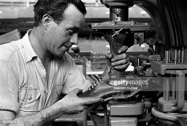 Worker putting the finishing touches to the inside of a children's shoe at the Gleneagles factory of the Saxone Shoe Company in the Scottish town of...