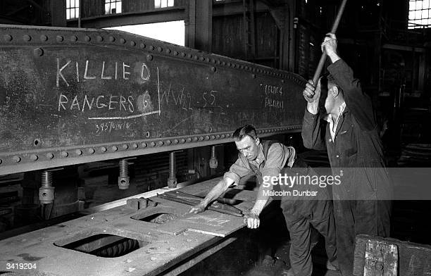 Two men at work in a factory in the Scottish industrial town of Kilmarnock A blackboard above them carries the score at a local football match...