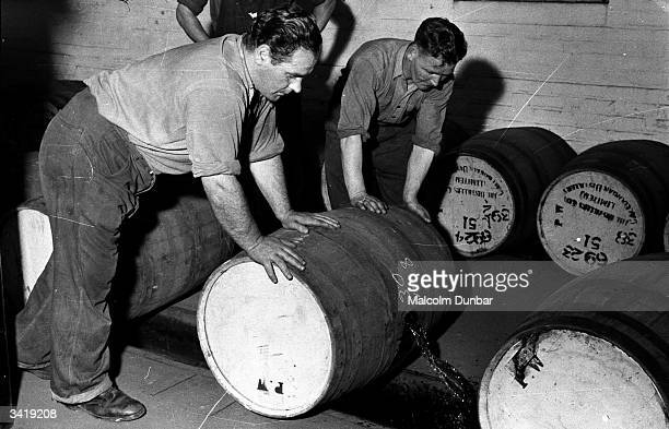 Workers rolling barrels of whisky along the floor at Johnnie Walker's distillery in the Scottish industrial town of Kilmarnock The Johnnie Walker...