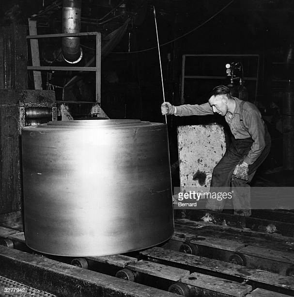 An employee of the Abbey Steelworks of Port Talbot measures a roll of steel