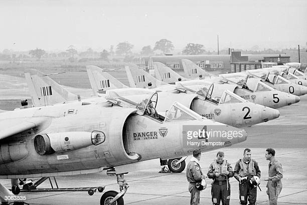 A group of pilots on the tarmac next to a row of Kestrels or jump jets which bear the linked insignia of Britain West Germany and the USA The Kestrel...