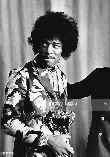 Influential rock guitarist singer and songwriter Jimi Hendrix holds an award which he has just received from Radio One DJ Jimmy Savile
