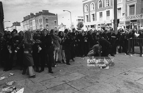 A crowd of fans held back by a line of policemen eagerly await the American pop group The Osmonds outside the Rainbow Theatre Finsbury Park north...