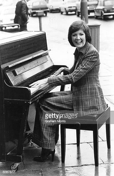 Thames Television's new signing entertainer Cilla Black has a laugh banging out a tune on an old piano in a London street