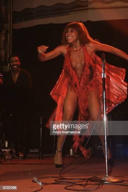 Singer Tina Turner wears a lowcut red cabaret costume with fringe and a pleated red cape while performing onstage at the Ritz in New York City