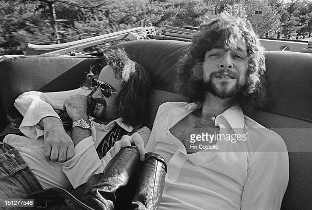 Bassist John McVie and guitarist Lindsey Buckingham of BritishAmerican rock band Fleetwood Mac posed sitting in a vintage car outside a recording...