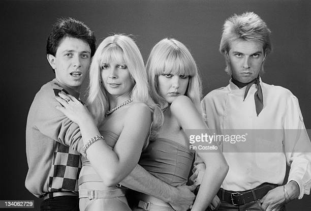 English pop duo The Quick pose with two female models in a studio portrait session in London in October 1979