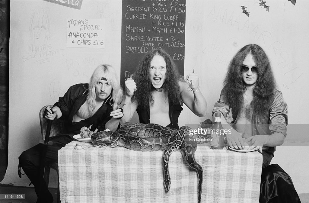 Heavy Metal band Venom posed with snakes on a cafe table in London in October 1985. Left to right: guitarist Jeffrey 'Mantas' Dunn, bassist Conrad 'Cronos' Lant and drummer Anthony 'Abaddon' Bray.