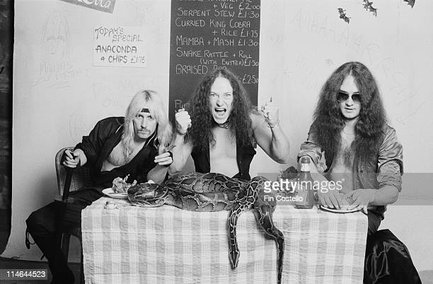 Heavy Metal band Venom posed with snakes on a cafe table in London in October 1985 Left to right guitarist Jeffrey 'Mantas' Dunn bassist Conrad...