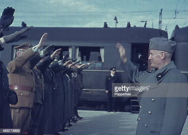 Italian Prime Minister Benito Mussolini takes a salute from Axis officers at the railway station in Florence Italy during a visit by German...