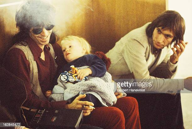 Keith Richards of the Rolling Stones holds his son Marlon Richards alongside drummer Charlie Watts at Schiphol airport Netherlands in October 1970