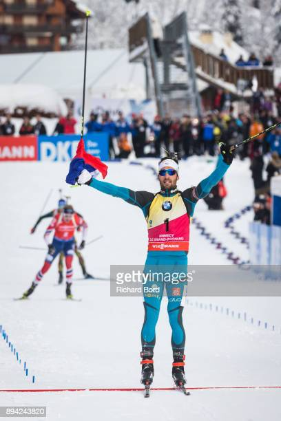 1st place Martin Fourcade of France celebrates as he passes the finish line during the IBU Biathlon World Cup Men's Mass Start on December 17 2017 in...