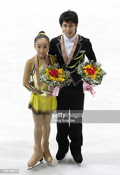 1st place winner Wenjing Sui and Cong Han of China pose on the ice after the medals ceremony of the Pairs Free of the 2011 World Junior Figure...