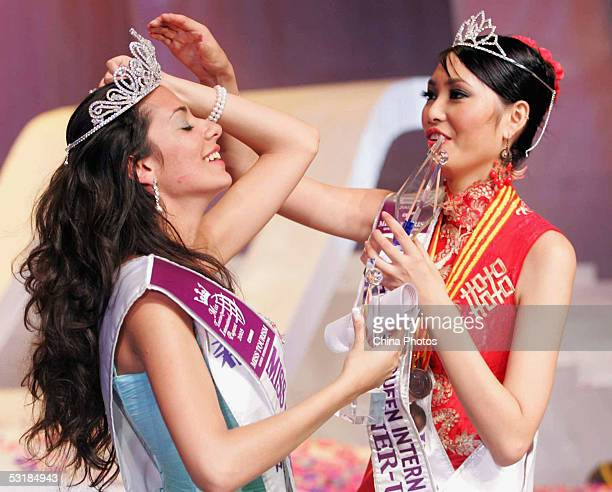 1st runnerup Sun Jia from China helps the champion Nikoletta Ralli from Greece fix her crown after the Miss Tourism Queen International 2005 World...