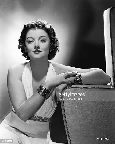 American actress Myrna Loy wearing a white gown and two bracelets