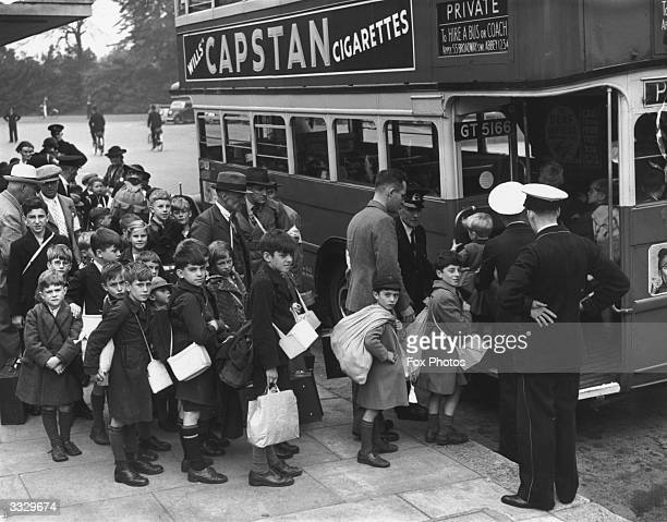 Evacuee children carrying their gas masks boarding a bus to leave London for the countryside a few days before Britaind entered WW II