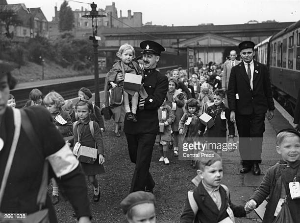 Police and railwaymen assist some of the 800 evacuee children as they leave Ealing Broadway station, London, for the country, on the first day of...