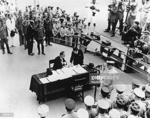 Japanese Foreign Minister Mamoru Shigemitsu signs the Japanese surrender on board the USS Missouri in Tokyo Bay, while General Douglas MacArthur ,...