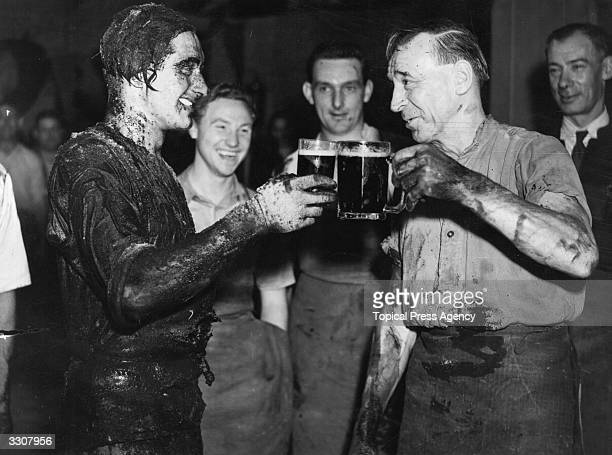 P Newton right toasting his pupil apprentice cooper R A Barban after his passing out ceremony at Watney's Stag Brewery Mortlake London During the...