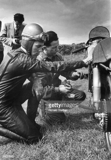 Geoff Duke who won both the Junior and Senior World Grand Prix Motorcycle Championships checks his Norton machine before the start of a race at...