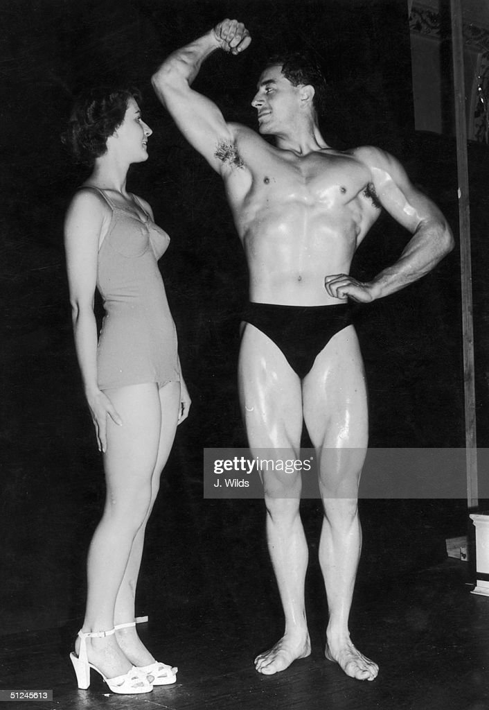 1st September 1951, Mr Universe contestant Arnold Dyson of Liverpool shows off his pecs and biceps to an admiring Norma Tinkler, an entrant in the Junior Miss Britain contest, at the Royal Hotel, London.