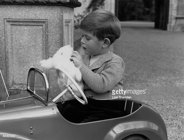 Prince Charles eldest son of Queen Elizabeth II and the Duke of Edinburgh playing with a glove puppet in his toy car whilst staying at Balmoral