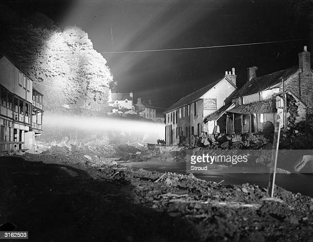 Searchlights illuminate a flooded area of Lynmouth in Devon after a catastrophic deluge which resulted in several deaths