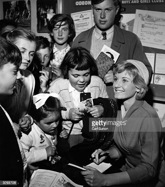 The actress Jill Ireland singing autographs at the Boys and Girls Club exhibition at the Odeon Cinema
