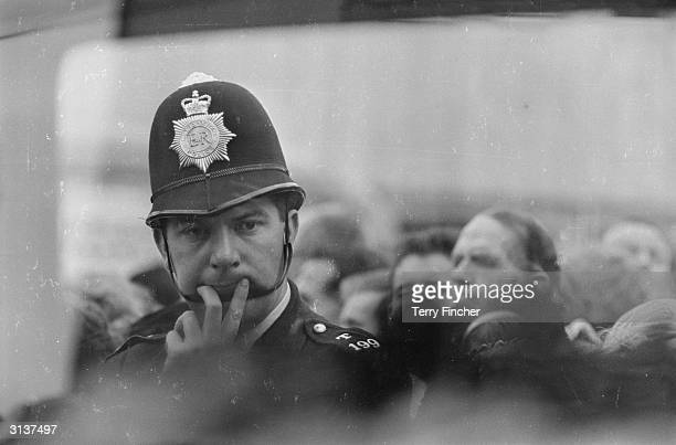 A policeman attends the funeral of three colleagues shot down in the line of duty at the church of St Stephen with St Thomas on the Uxbridge Road...