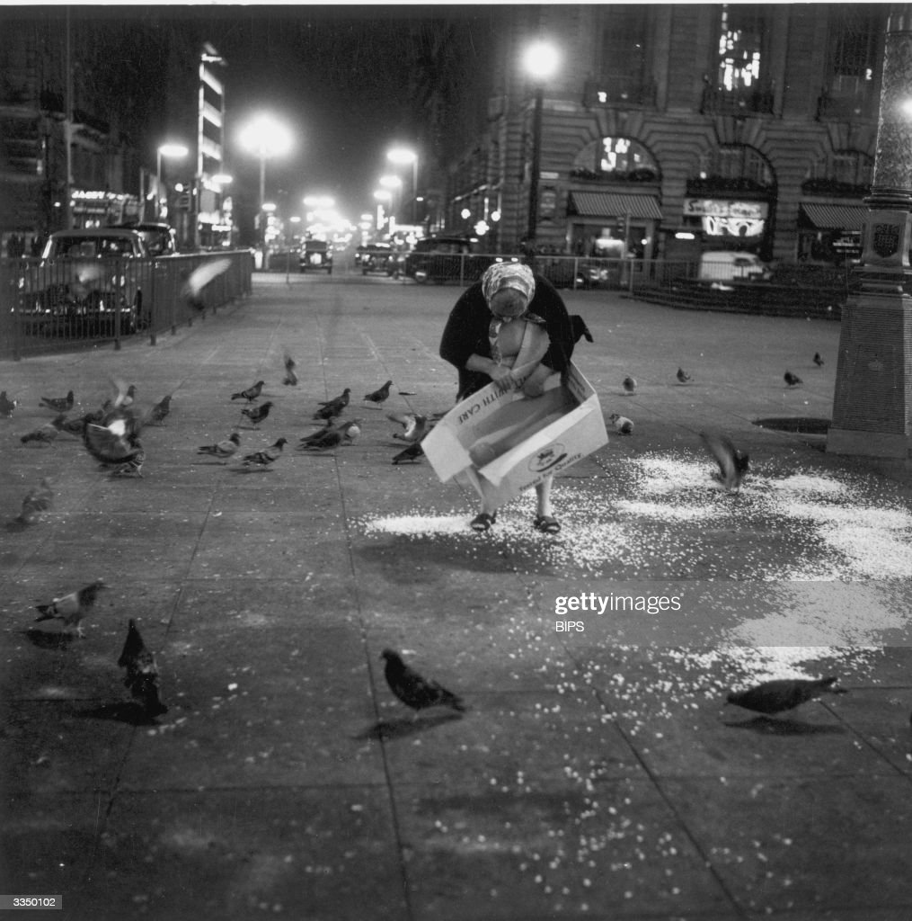 An old woman feeds the pigeons from a cardboard box in a square of London's Soho district.