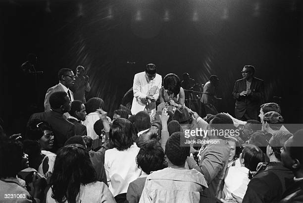 American RB singer Aretha Franklin bending down onstage to shake hands with a crowd of fans at the 'Soul Together' concert at Madison Square Garden...