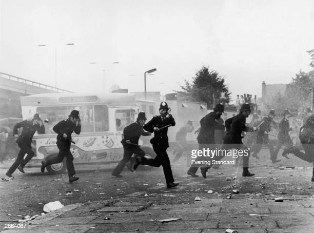London police make a tactical withdrawal during the riots which followed the Notting Hill Carnival