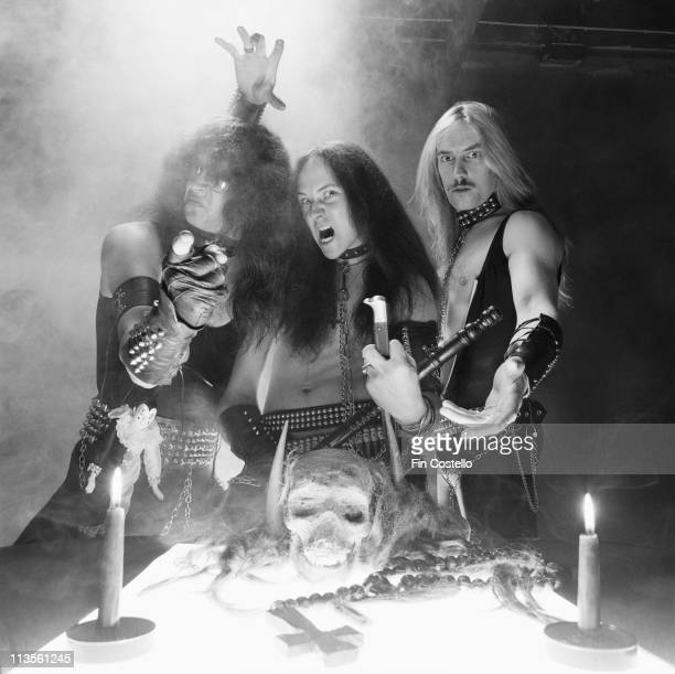 English Thrash metal band Venom posed with candles a cross and skull in London in September 1982 Left to Right Tony 'Abaddon' Bray Conrad 'Cronos'...