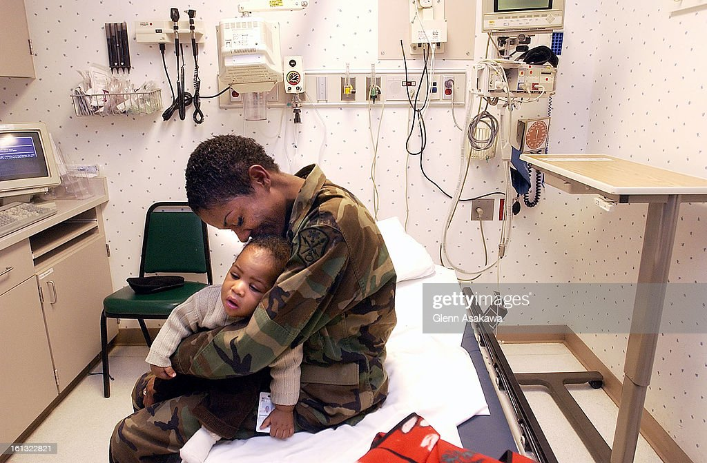 AURORA, CO, DECEMBER 4, 2003--Nicole <cq> Flythe <cq> cradles her 7-month-old son, George III, while waiting in an examination room on a recent weekday evening at the Medical Center of Aurora pediatric emergency room. Flythe, who is stationed at Buckley A : News Photo