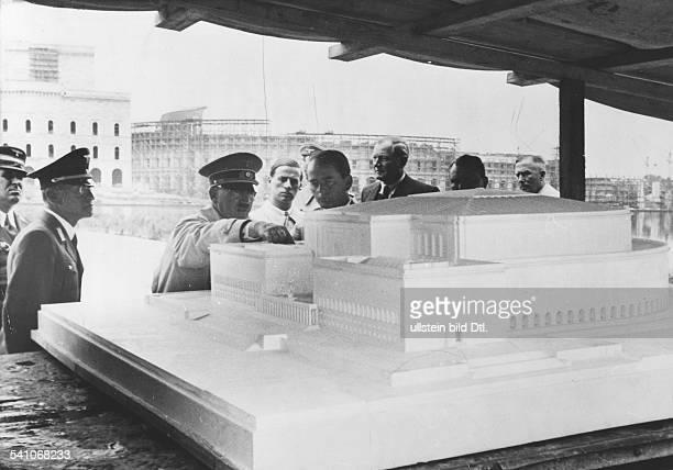 *20041889Politiker NSDAP D auf dem Gelände des Reichsparteitags inNürnberg vor dem Modell der neuenKongresshalle imHintergrund der begonnene Bau...