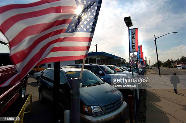 DENVER COLORADO OCTOBER 4 2005Flags fly over cars for sale at a used car dealership at Colfax Ave and Dahlia St in Denver recently