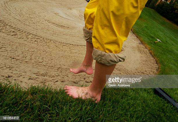 PINES COLORADOAUGUST 4 2005Grounds crew member Rebecca Fritzler <cq> goes barefoot to clear the water from the bunkers on the 1st green at the 20th...