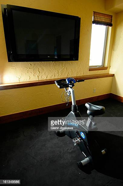 """An interactive """"Game Bike"""" sits in front of a flatscreen monitor in the exercise room in the Villa Ispirata <cq> home built by Pinnacle Peak Custom..."""