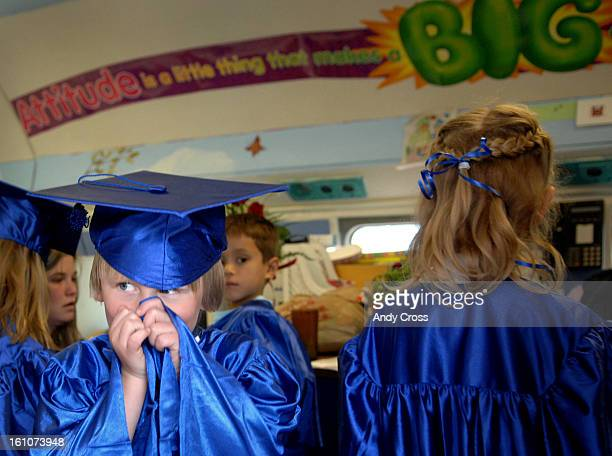 DENVER COMAY 23RD 2007KINDERGARTENGRADbKindergarten student Samuel Houghton <Cq> left hides his face after putting on his cap and gown inside an old...