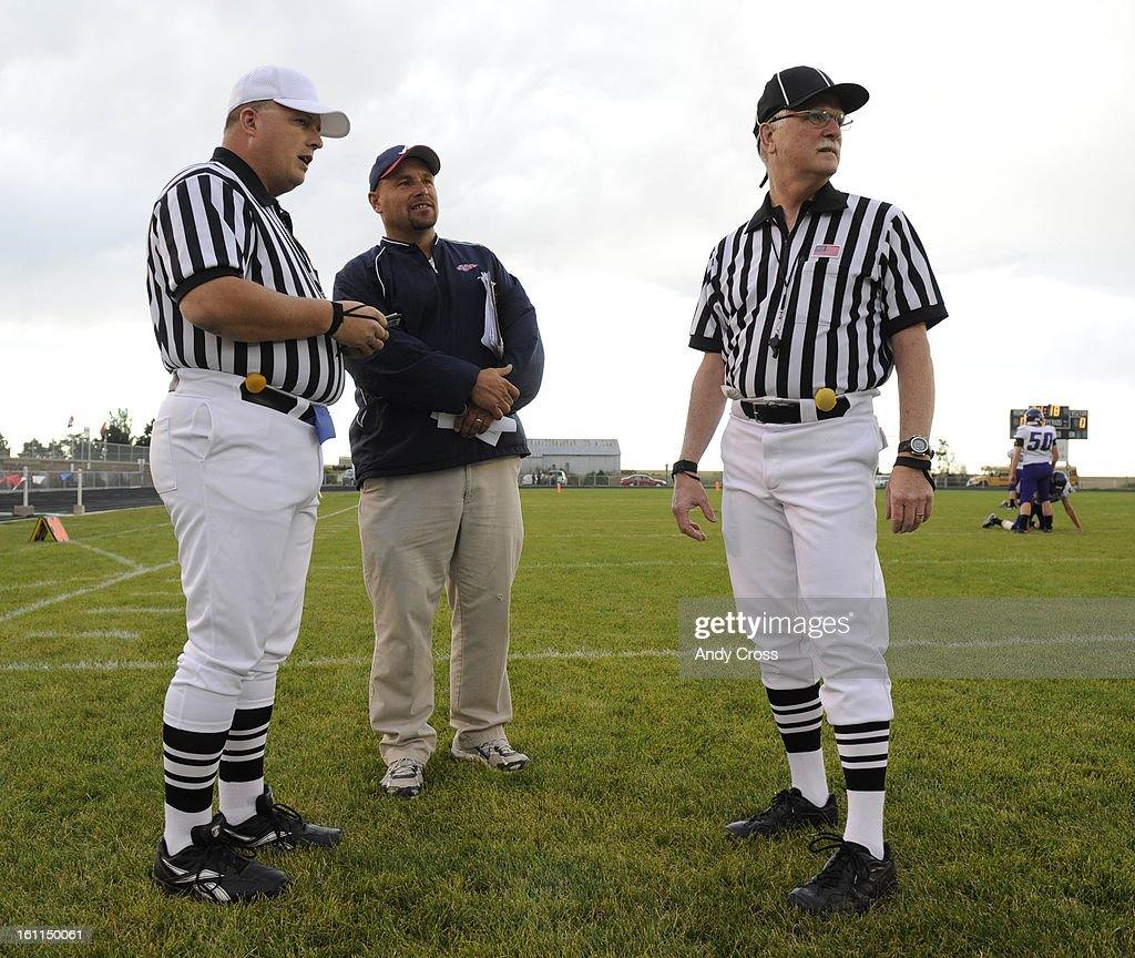 AKRON, CO--SEPTEMBER 10TH 2010--Akron High School head football coach, Brian Christensen, center, talks with referee, Mike Billadeau, left, and official, Jim Short, before the game against Rye at Akron Friday evening. Andy Cross, The Denver Post : News Photo