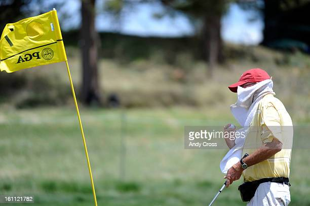 COMAY 26TH 2010Caddie for professional golfer Jeff Sluman Jimmy Walker tries to get a towel off of his face in strong winds during a practice round...
